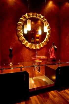Un gran espejo refleja la luz creando la ilusión de espacio en un baño pequeño