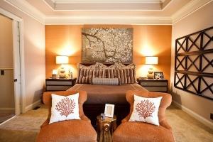 Una pared con un suave color mandarina da calidez al dormitorio principal.